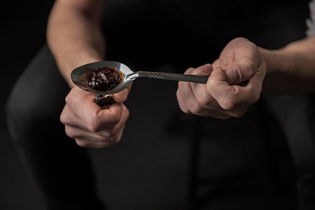 Close up of man arms melting narcotic in spoon. Unhealthy life concept Stock Photo