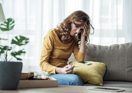 좌절과 임신 테스트 스틱보고 걱정 된 소녀. 그녀는 거실 소파에 앉아있다. 스톡 콘텐츠
