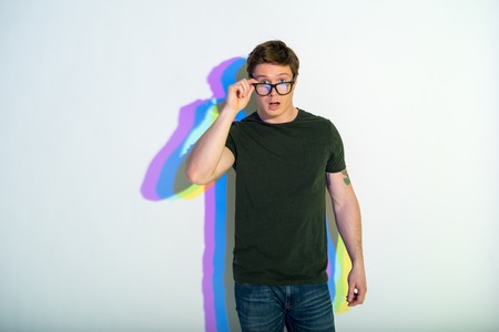 Portrait of surprised male keeping glasses while looking at camera. Multicolored shadow. Astonishment concept