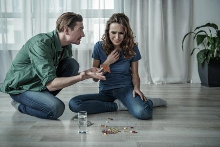 それはなんですか。ショックを受けた男は、女性が床に座って泣いている間、別の錠剤を見ています。自殺の概念を犯す