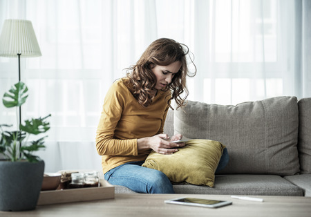 Nervous young woman is touching message on smartphone while sitting on sofa. Pregnancy test stock is on table Stock Photo