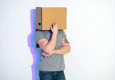 Nadenkend mannetje met geschilderd weerspiegelings verbergend gezicht binnen kartondoos. Dromerigheid concept Stockfoto