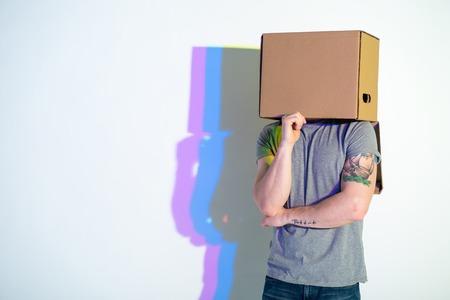 Nadenkend mannelijk verbergend gezicht binnen kartondoos. Abstractie concept. Kopieer ruimte