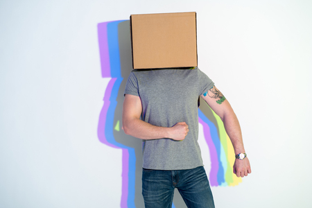 Man with carton on head going while gesticulating hands. Positive concept