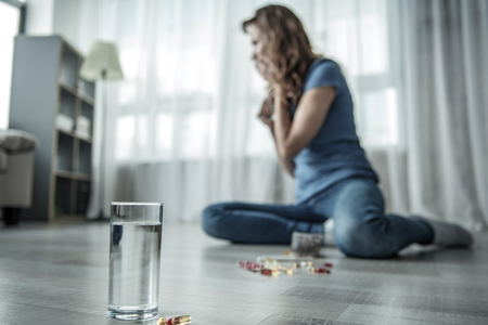 Stressful young woman wants to commit suicide. She is sitting on floor and crying. Focus on glass of water and drugs 写真素材