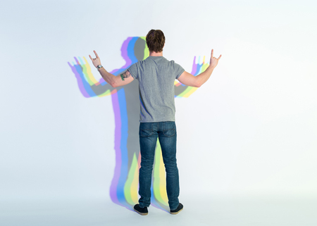 Full length young male demonstrating rock and roll sign by hands. He turning back to camera. Signifier concept Stock Photo - 94828168
