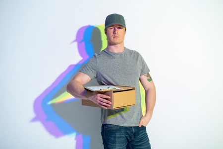 Portrait of calm courier with multicolored shadow keeping parcel. He putting hand in pocket. Delivery concept Stock Photo