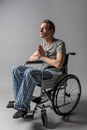 Serene religious man sitting in wheelchair and holding palms together. He is worshipping