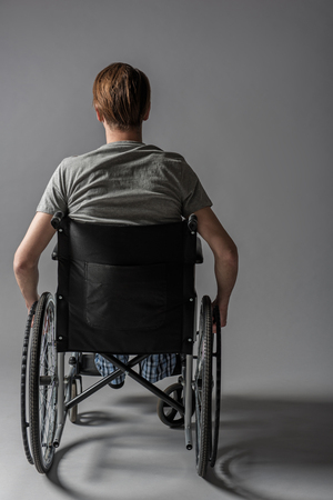 Back of guy with physical inability sitting in wheelchair. He is holding his hands on wheels Imagens - 94828451