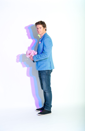 Full length portrait of calm man with painted reflection keeping bouquet of flowers. Romance concept