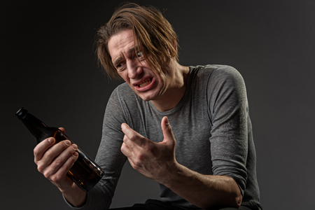 Waist up portrait of man with alcohol dependence looking at bottle with perplexity. Isolated on background Stock Photo