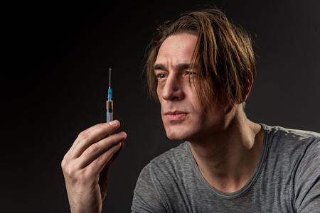 Retrato del hombre joven del drogadicto que sostiene y que mira la jeringuilla con seriedad. Aislado en el fondo
