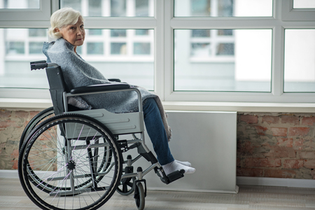Upset mature woman looking at camera with sad look. She is sitting in wheelchair in room wrapped in a blanket. Copy space in right side Stock Photo