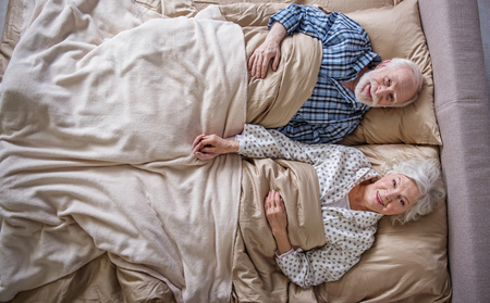 Top view of happy elderly husband and wife lying in bed. They are looking at camera with smile. Concept of peace Stock Photo