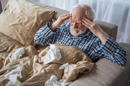 How it hurts. Exhausted old male having headache in bedroom. He is sitting in bed and holding his head with tired look