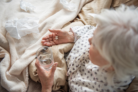Top view of old woman holding pills and glass of water. Focus on her hand. She is sitting in bed and looking at her hands