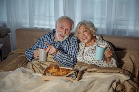 Cheerful old husband and wife having rest at home. They are eating croissant and drinking tea while sitting in bed and watching TV Stock Photo