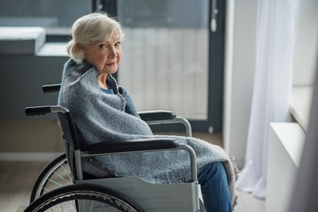 Cheerless senior female sitting in invalid chair in front of the window. She is looking at camera with sad look