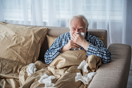 Sick senior man suffering from illness. He is sitting in bed covered with blanket and blowing his nose with tired look. Copy space in left side