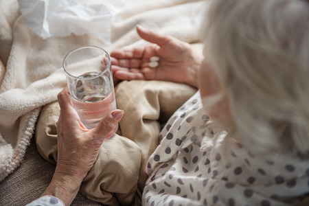 Top view of senior female sitting in bed. Focus on her hand. She is holding medicine and glass of water and looking at her hands