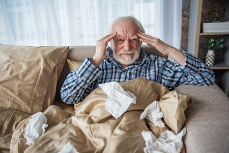 Depressed senior man looking at camera with tired look. He is suffering from migraine at home and holding his head while sitting in bed