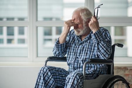 Maschio senior triste che si siede in sedia a rotelle nella sala con il fronte senza speranza. Si tiene gli occhiali e si tocca il ponte del naso Archivio Fotografico