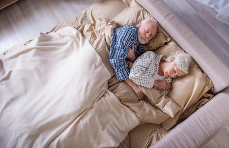 Dulces sueños. Vista superior de calma anciano marido y mujer acostado en el dormitorio. Sus ojos están cerrados. Los pensionistas se relajan en la cama y se abrazan