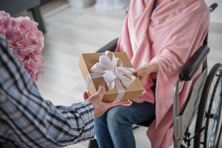 Man giving a present to his wife. She is sitting in wheelchair and he is standing near the chair and holding flowers. They are holding the box with bow. Focus on close up box