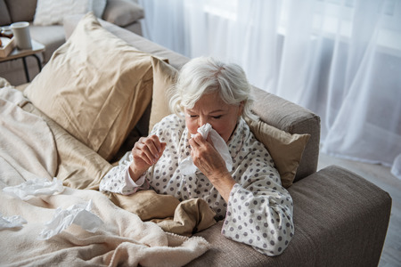 Exhausted old female having migraine and blowing her nose. She is sitting in bed and holding her head with tired look. Copy space in left side