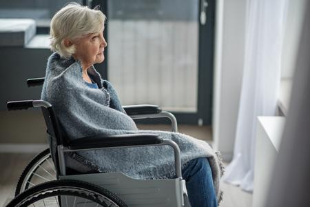 Schwermütige ältere Frau, die draußen mit Sehnsuchtsblick schaut. Sie sitzt im Rollstuhl in einem Raum, der in eine Decke gewickelt ist Standard-Bild
