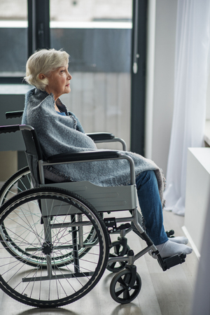 Cheerless senior female sitting in invalid chair with sad look. She is wrapped in a blanket and looking outside Stock Photo