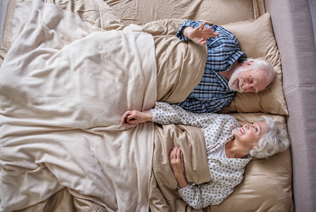 Good morning. Top view of calm senior couple waking up in the morning. They are looking at each other and holding their hands in bedroom