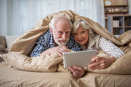 Glad senior husband and wife looking at camera and smiling. They are looking out from under the blanket. Man is holding the device