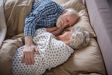 Pleased elderly couple lying in bed. Old woman and man looking at each other and smiling while embracing