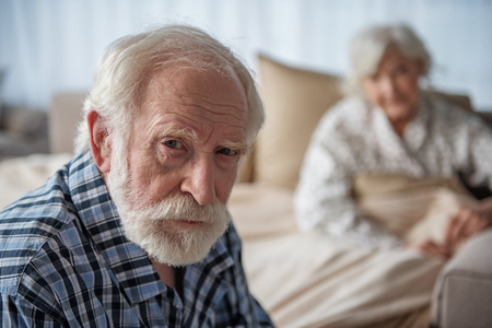 Portrait of depressed old pensioner looking at camera with upset look. Focus on his face. His wife is sitting in bed on background