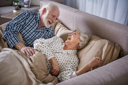 Cheerful old husband and wife looking at each other and laughing. They are lying in bedroom in the morning