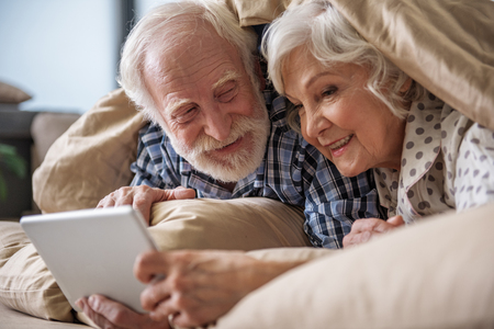 Happy old married couple lying in bed under blanket and holding the tablet. Woman is looking at the screen and smiling. Man is looking at his wife with smile