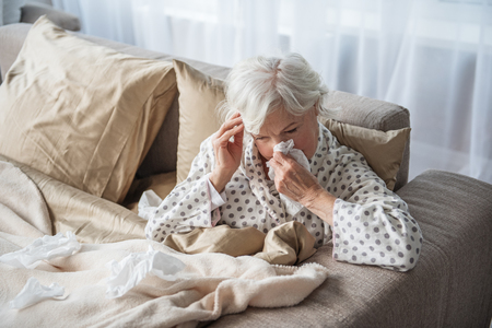 Sick mature woman blowing her nose and holding her head with tired look. She is sitting in bed covered with blanket. Copy space in left side