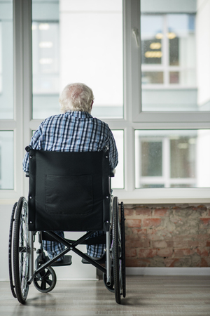 Senior male is sitting in wheelchair in front of the window in room. He is looking outside. Concept of loneliness. Copy space in right side Archivio Fotografico