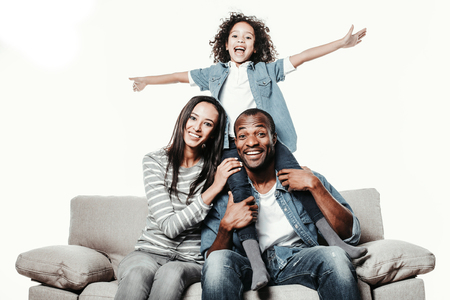 Portrait of happy parents and kid rejoicing on comfortable divan. Child is sitting on fathers shoulders with hands up. Isolated on background