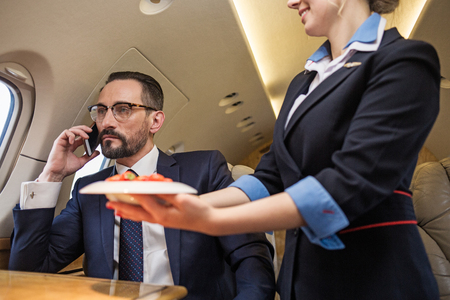 Portrait of thoughtful good looking mature man talking by phone in airplane. Stewardess is serving plate of strawberries