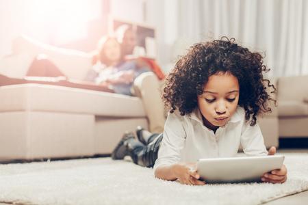 부드러운 tapis에 휴식하는 동안 태블릿을보고하는 사려 깊은 아이. 여자에 중점을 둡니다. 배경에 부모