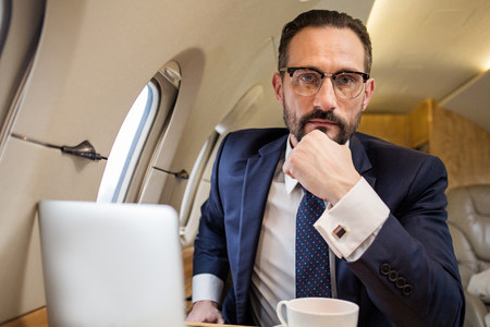 Portrait of serious handsome male in aircraft cabin sitting in his seat and looking at camera Stock Photo