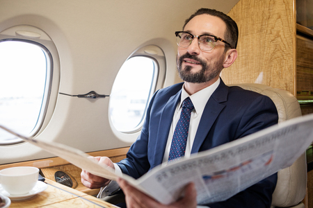 Portrait of stylish bearded male in airplane cabin holding newspaper and smiling