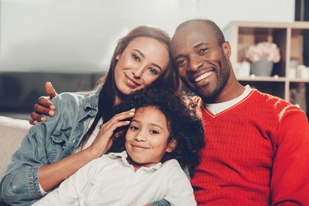 Portrait of happy mother, father and daughter sitting together at home, looking at camera and smiling