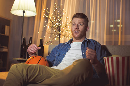 Portrait of surprised unshaven male looking basketball game while locating on couch in room. Rest concept Stock Photo