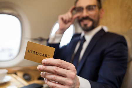 Portrait of happy rich man in aircraft cabin holding gold card in hand and laughing. Focus on plastic