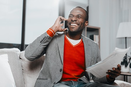 Waist up portrait of pleased guy holding documents while using mobile phone with joy. He is sitting inside Stock Photo