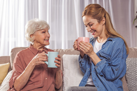 Cheerful female pensioner and beaming adult daughter tasting cups of tea in living room. Coziness concept