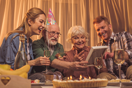 Portrait of cheerful lady with beaming male sitting near glad grandmother and grandpa. They watching at photo during party. Enjoyment concept